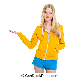 Happy teenager girl presenting something on empty palm