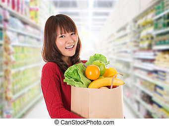 Asian woman shopping in a grocery store - Beautiful young...