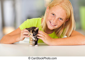 lovely pre teen girl with pet kitten at home