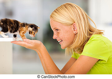 loving teen girl playing with pet kitten at home