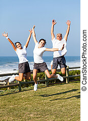 active family jumping at the beach