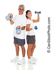 senior couple posing with various gym equipment - cheerful...