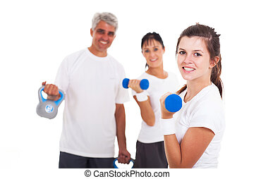 young girl exercising in front of her parents - cheerful...