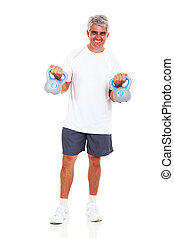 middle aged man exercising with kettle bells
