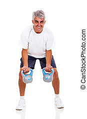 senior man working out with kettle bells, isolated on white