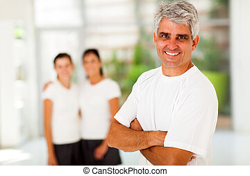 sporty mature man in front of family