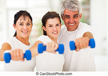 portrait of fit family having fun with dumbbells at home