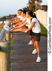 family stretching at the beach before jogging - active...