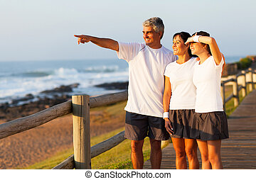middle aged man pointing at ocean with family in the morning