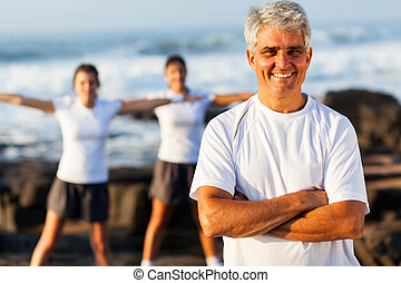 fit mature man on beach with family exercising on background