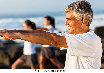 side view of middle aged man exercising - side view of...
