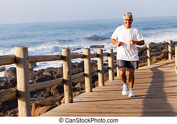 fit senior man running at the beach - cheerful fit senior...