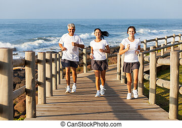 fit family jogging at the beach - cheerful fit family...