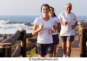 healthy family jogging on beach - happy healthy family...