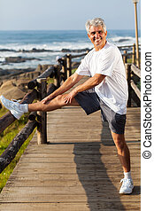 active mature man stretching leg at the beach