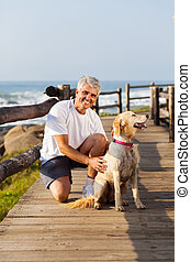 active senior man and his dog at the beach - active senior...