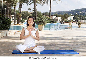 Woman meditating in lotus yoga - A middle aged woman in...