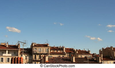 sky with a few clouds and building tops in marseille, france