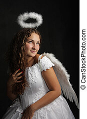 White angel - Pretty young woman in angel dress over dark...