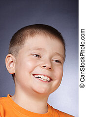 Toothy smile - Boy in orange shirt smiling photo with...