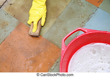 gloved hand cleaning of dirty filthy floor - Hand in yellow...