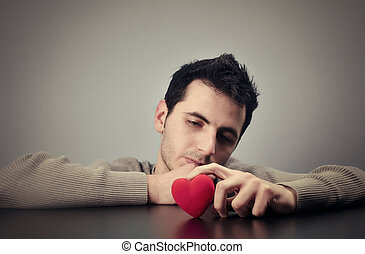 Love problems - Young man looking at a heart with a sad look