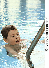 Boy swimming in pool holding metallic hand-rails