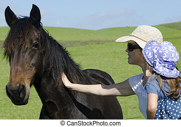 Horse farm - Mother and daugther pat a black horse in a...