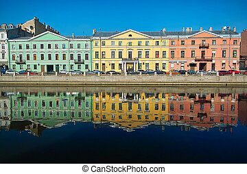 Three multicolor old houses on the river quay