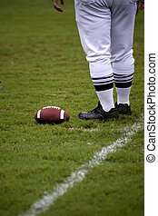 Legs of football official as he stands next to a football...