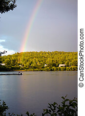 Sunny and rainy skys with a rainbow over a lake