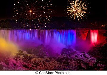 Rainbow colored Niagara Falls with fireworks display