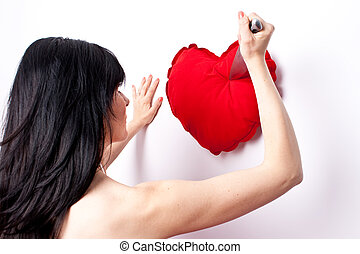 Heart broken - Woman pointing a knife at a heart shaped...