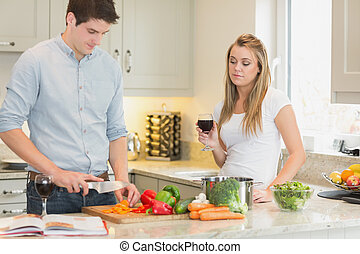 Man cooking with woman drinking red wine