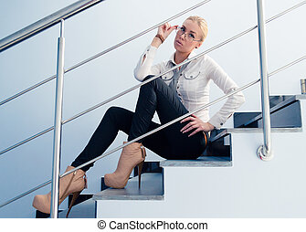 Young business fashion woman sitting on stairs