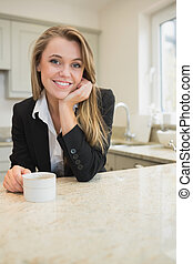 Woman drinking coffee at morning in kitchen