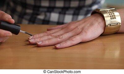 Woman apply top coat nail polish