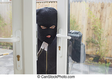 Burglar opening the door with crowbar