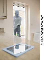Burglar looking at tablet pc through kitchen door - Burglar...