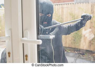 Burglar opening the door with a crowbar - Burglar in garden...