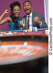 Couple sitting cheering at roulette wheel