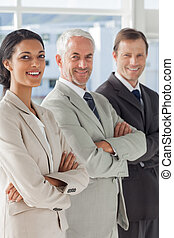 Three smiling business people standing together with their...