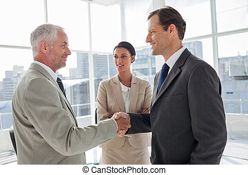 Businesswoman introducing colleagues together in their...