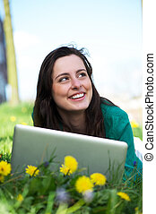 Happy young woman working on laptop outdoors - Portrait of a...