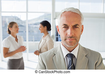 Serious businessman standing while colleague are discussing...