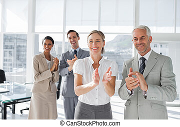 Group of business people applauding together during a...