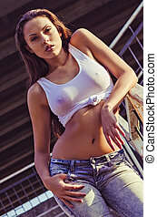 Beautiful young girl in shirt and jeans stands on stairs at...