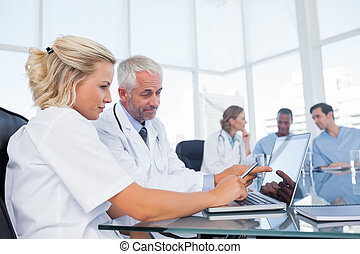 Doctors using a laptop in a bright office
