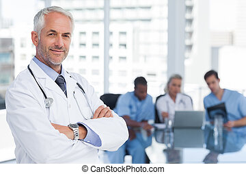 Doctor with arms folded standing in front of his team