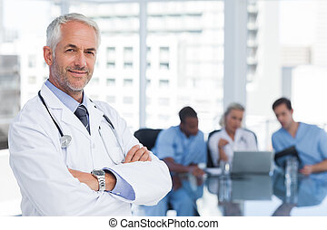 Smiling doctor with arms folded standing in front of his...
